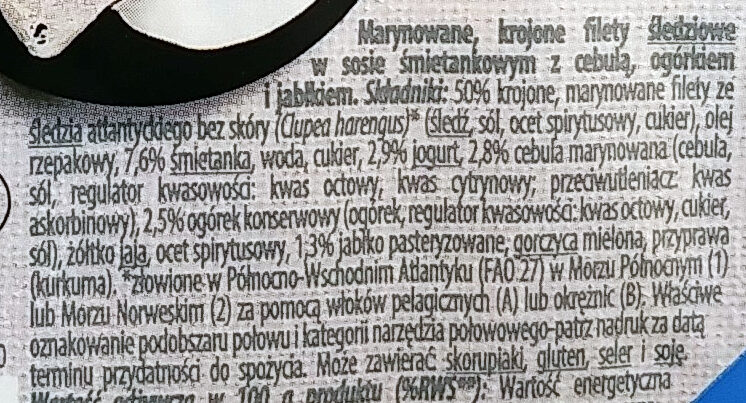 Marynowane, krojone filety _śledziowe_ w sosie śmietankowym z cebulą, ogórkiem i jabłkiem. - Składniki - pl