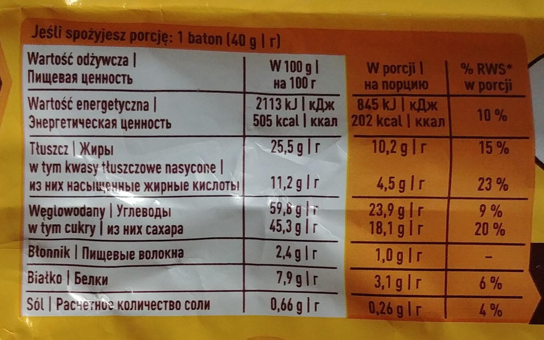 Nadziewany wafel z karmelem 29.8%, płatkami pszennymi 3,2%, i orzechami ziemnymi 18% w polewie kakaowej. - Wartości odżywcze